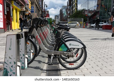 Montreal, Canada - August 10, 2019: Bixi bikes stand on Saint Catherine Street.  Bixi bikes is a public bike sharing system launched in Montreal in 2009 purchased by the city in 2014.