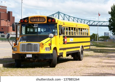 MONTREAL, CANADA - AUGUST 18: school bus waits in a parking at Quai de l'Horloge on August 18, 2008 in Montreal, Canada. In the background from left the Molson Brewery and Jacques Cartier bridge.
