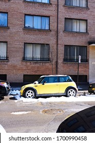 Montreal, Canada - Circa March, 2020: Bright yellow MINI Cooper is parked at downtown street. BMW, current maker of Mini transformed the classic car to modern vehicle.