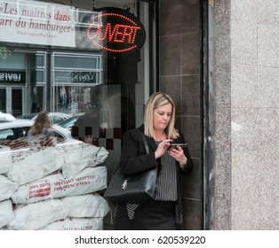 MONTREAL, CANADA - CIRCA OCTOBER 2016: Young woman seen using a cell phone, probably texting by a shop window with reflections of the adjacent street seen.