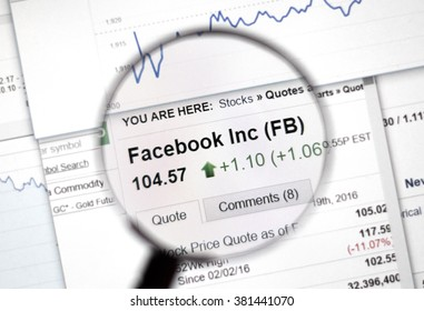 MONTREAL, CANADA - FEBRUARY, 2016 - FB - Facebook stock market ticker with charts under magnifying glass.
