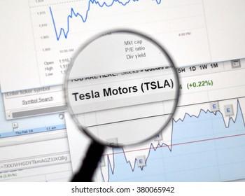 MONTREAL, CANADA - FEBRUARY, 2016 - TSLA - Tesla Motors stock market ticker with charts under magnifying glass.