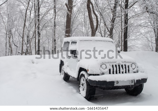 Montreal, Canada - February 2020: Frontview of a Jeep-like SUV covered by snow parked in a forest in winter
