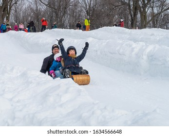 Montreal, Canada - february 2020 : man and children having fun on a sledge at the mount Royal park