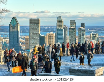MONTREAL, CANADA - JANUARY 1, 2019 : Scenic view of downtown Montreal in winter from Mount Royal Chalet, and people taking pictures and making selfies.
