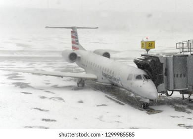 Montreal, Canada - January 20, 2019: An American Eagle airplane sits grounded at a gate at Montréal-Pierre Elliott Trudeau International Airport during a snowstorm. Temperatures dropped to -30c.