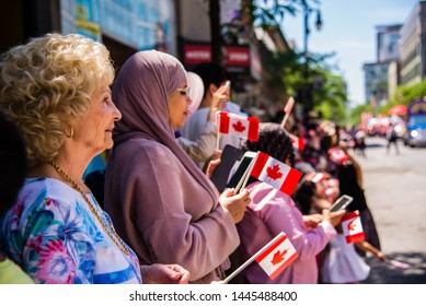 Montreal, Canada - July 1 2019: People gathering at downtown Montreal watching the Canada Day Parade