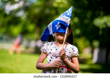 Montreal, Canada - July 24 2017: Little girl waving the Quebec Flag in Quebec day Parade in Montreal downtown