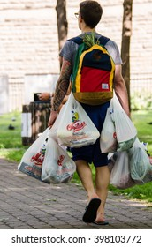 Montreal, Canada - July 26, 2014: A young man walking invents a clever way to carry many grocery bags in Montreal, Canada
