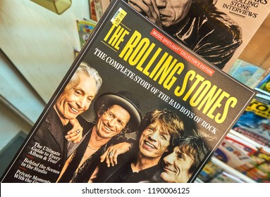 MONTREAL, CANADA - JULY 9, 2018: Rolling Stone magazine in a hand over a stack of magazines. Rolling Stone is an American magazine which focuses on popular culture.