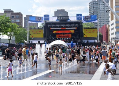 MONTREAL, CANADA - JUN 13, 2015: Children cool off in the fountains on a hot day at the annual Les FrancoFolies de Montreal festival at Place des Arts section of Centre-ville
