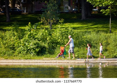 MONTREAL, CANADA - JUNE 17, 2018: A family walking near the pond in La Fontaine Park, Montreal, Canada. Father is pushing the stroller of an infant and two little girls are following. Editorial use.