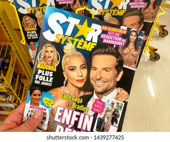 MONTREAL, CANADA - JUNE 20, 2019: A hand holding Star Magazine with Lady Gaga and Bradley Cooper on the cover. Star is American celebrity tabloid magazine founded in 1974 and owned by American Media