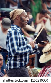 Montreal, Canada - June, 2018. African American male percussionist plays rhythm with a cow bell at Tam Tams festival in Mount Royal Park, Montreal, Quebec, Canada. Editorial use.