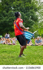 Montreal, Canada - June, 2018. Male African percussionist plays djembe drum bongo in front of the audience at Tam Tams festival in Mount Royal Park, Montreal, Quebec, Canada. Editorial use.
