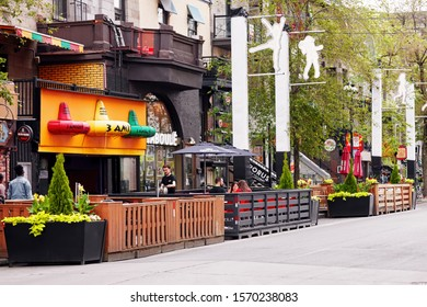 Montreal, Canada - June, 2018: People sitting at cafes and bars on famous landmark St. Denis street in Montreal, Quebec, Canada. Editorial.