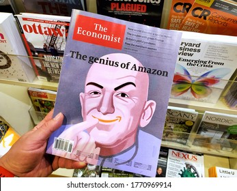 Montreal, Canada - June 30, 2020: The genius of Amazon title and a picture of Jeff Bezos as the Dr Evil on The Economist newspaper in a hand over a stack of magazines.