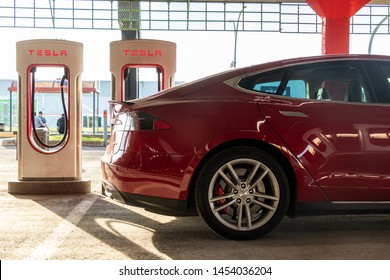 MONTREAL, CANADA - June 9, 2019: Red Tesla Model S charging at Montreal Tesla Supercharger Stall at Place Vertu Shopping Centre during a bright sunset.