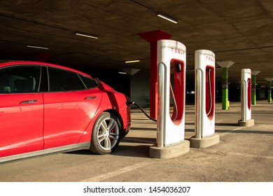 MONTREAL, CANADA - June 9, 2019: Red Tesla Model S plugged-in at Montreal Tesla Supercharger location at Place Vertu Shopping Centre during a bright sunset.