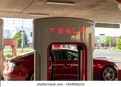 MONTREAL, CANADA - June 9, 2019: Top of Tesla Supercharger stall with Red Tesla Model S charging in the background.