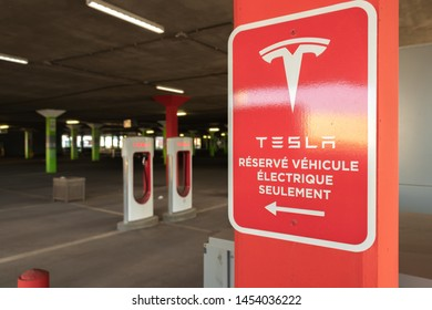 """MONTREAL, CANADA - June 9, 2019: Tesla """"Réservé Véhicule Électrique Seulement"""" (Reserved for Tesla Electric Vehicles Only in English) sign at Tesla Supercharger with charging stalls in background."""