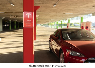 """MONTREAL, CANADA - June 9, 2019: Tesla """"Réservé Véhicule Électrique Seulement"""" (Reserved for Tesla Electric Vehicles Only in English) sign at Tesla Supercharger with Red Tesla Model S charging beside."""