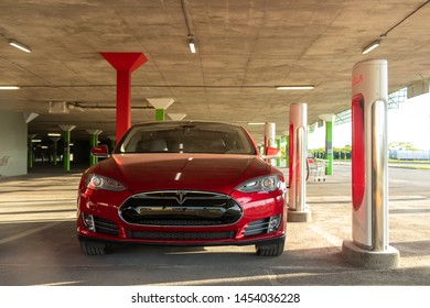 MONTREAL, CANADA - June 9, 2019: Front-view of Red Tesla Model S supercharging at Tesla Supercharger Station in Montreal, Quebec.