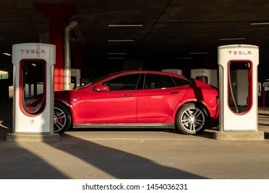 MONTREAL, CANADA - June 9, 2019: Side-view of Red Tesla Model S parked, charging at Tesla Supercharger in Montreal, Quebec located at Place Vertu Shopping Centre.