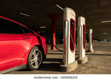MONTREAL, CANADA - June 9, 2019: Shining Red Tesla Model S plugged-in, charging at Montreal Tesla Supercharger location at Place Vertu Shopping Centre during sunset.