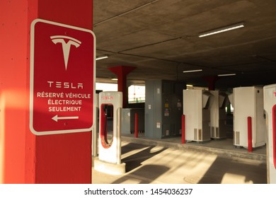 """MONTREAL, CANADA - June 9, 2019: Tesla """"Réservé Véhicule Électrique Seulement"""" (Reserved for Tesla Electric Vehicles Only in English) sign at Tesla Supercharger in Montreal, Quebec."""