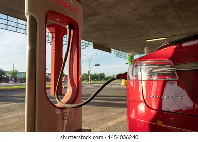 MONTREAL, CANADA - June 9, 2019: Tesla Model S plugged-in to Tesla Supercharging Stall in Montreal, Quebec.
