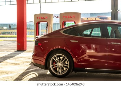 MONTREAL, CANADA - June 9, 2019: Red Tesla Model S charging at Montreal Tesla Supercharger location at Place Vertu Shopping Centre during a bright sunset.