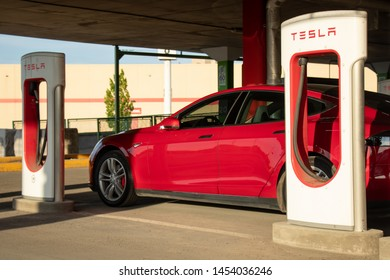 MONTREAL, CANADA - June 9, 2019: Red Tesla Model S parked at Montreal Tesla Supercharger location at Place Vertu Shopping Centre during sunset.