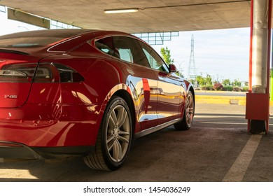 MONTREAL, CANADA - June 9, 2019: Red Tesla Model S parked at a covered Tesla Supercharger at Place Vertu Shopping Centre in Montreal, Quebec.