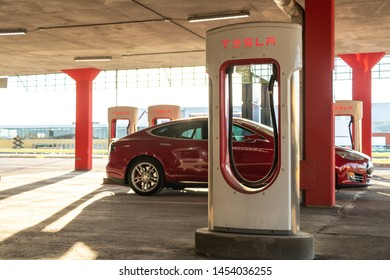 MONTREAL, CANADA - June 9, 2019: Tesla Supercharging Stall seen during sunset in Montreal, Quebec with Tesla Model S in background.