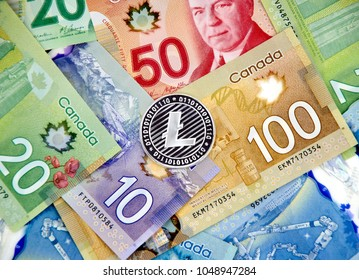 MONTREAL, CANADA - MARCH 10, 2018: Silver Litecoin cryptocurrency on canadian bank notes.