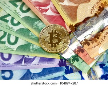 MONTREAL, CANADA - MARCH 10, 2018: Gold bitcoin cryptocurrency on canadian bank notes
