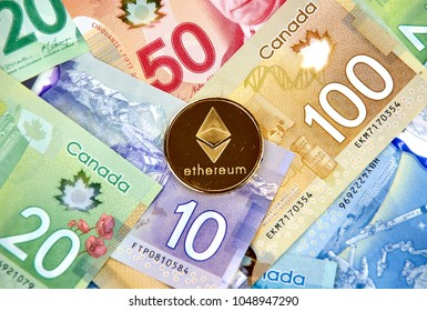 MONTREAL, CANADA - MARCH 10, 2018: Ethereum cryptocurrency coin and logo on canadian bank notes.