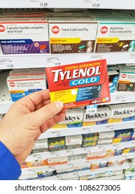 MONTREAL, CANADA - MARCH 10, 2018 : A hand holding Tylenol pack. Tylenol is a brand of drugs advertised for reducing pain, reducing fever, and relieving the symptoms of allergies, cold, headache
