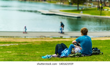 Montreal, Canada - May 12 2019: Young couple enjoying the afternoon by the lake of castor in Mont Royal of Montreal