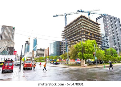 Montreal, Canada - May 26, 2017: Buildings in downtown area of city in Quebec region with construction crane with cars on road and people walking during wet rain on cloudy day