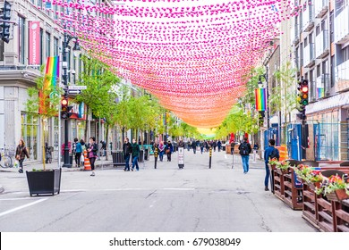Montreal, Canada - May 26, 2017: People walking on Sainte Catherine street in Montreal's Gay Village in Quebec region with hanging decorations
