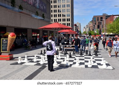 MONTREAL, CANADA - MAY 27, 2017: Unidentified people play chess on the giant chess board on Saint Catherine Street W in the downtown area.