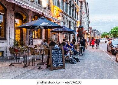 Montreal, Canada - May 27, 2017: Old town area with people sitting by street in evening outside restaurant called Delices du Monde in Quebec region city