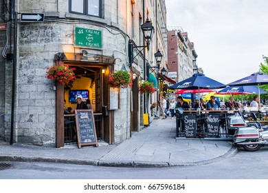Montreal, Canada - May 27, 2017: Old town area with people sitting by street in evening outside restaurant called La Creme de la Creme in Quebec region city