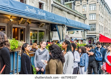 Montreal, Canada - May 27, 2017: Old town area Jacques Cartier square with people waiting in line queue outside restaurant called Jardin Nelson during evening in Quebec region city