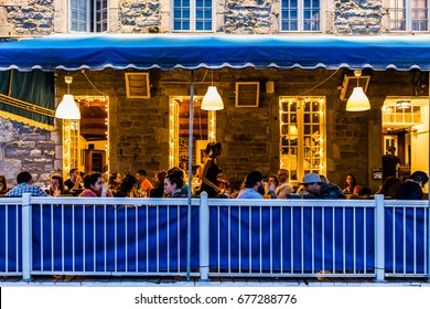 Montreal, Canada - May 27, 2017: Old town area with people sitting by street in evening night outside restaurant in Quebec region city