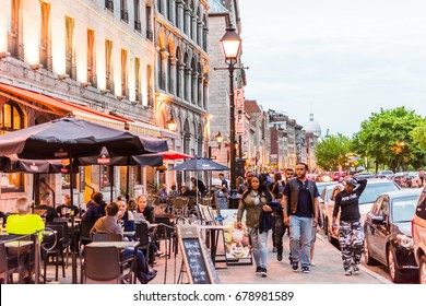 Montreal, Canada - May 27, 2017: Old town area with people walking up street in evening outside restaurants in Quebec region city
