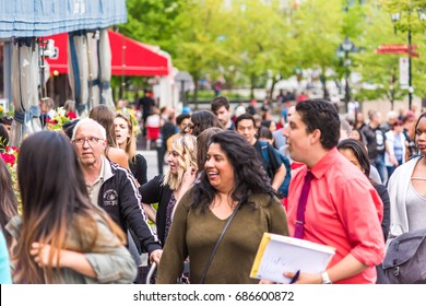 Montreal, Canada - May 27, 2017: Old town area with closeup of crowd of people walking up street laughing in evening outside restaurants in Quebec region city