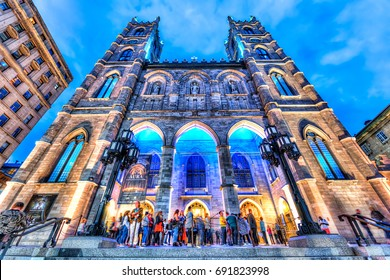 Montreal, Canada - May 27, 2017: Old town area with Notre Dame Basilica at night in evening outside in Quebec region city